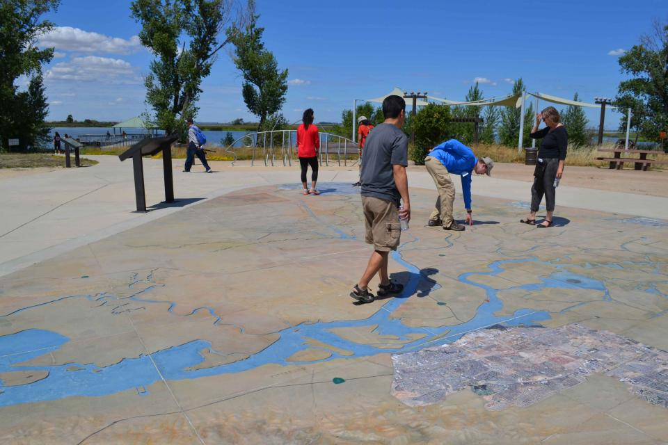 Visitors explore a large, three-dimensional map of the Sacramento-San Joaquin Delta at Big Break Regional Shoreline in Oakley.