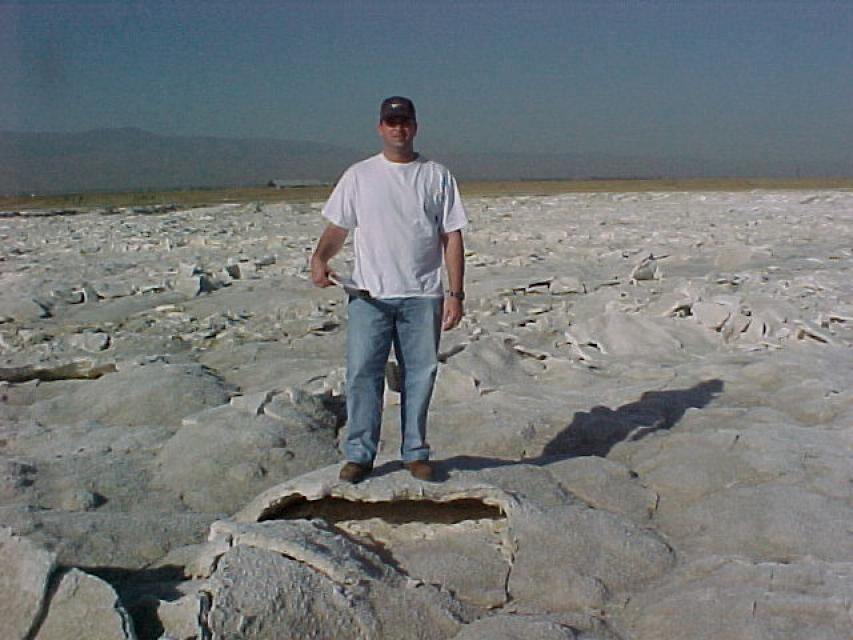 A man stands on an evaporation pond crusted with salt.