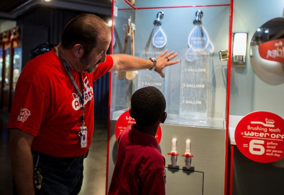 California Department of Water Resources employee Michael Miller explains low-flow shower heads to a young fair-goer as part of an indoor exhibit at the California State Fair in 2014.