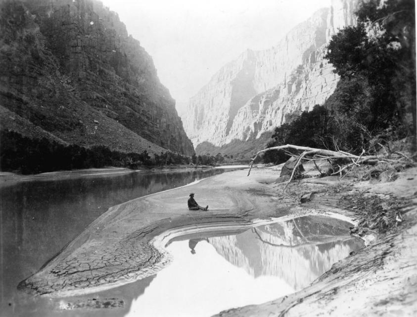 A member of Powell's second Colorado River expedition, seated and reflected in the Green River, 1871.