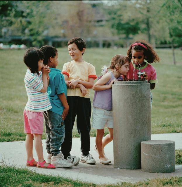 Children clustered around a drinking fountain.