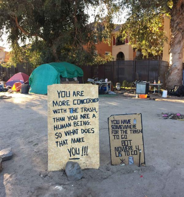 Signs posted by homeless people at an encampment.