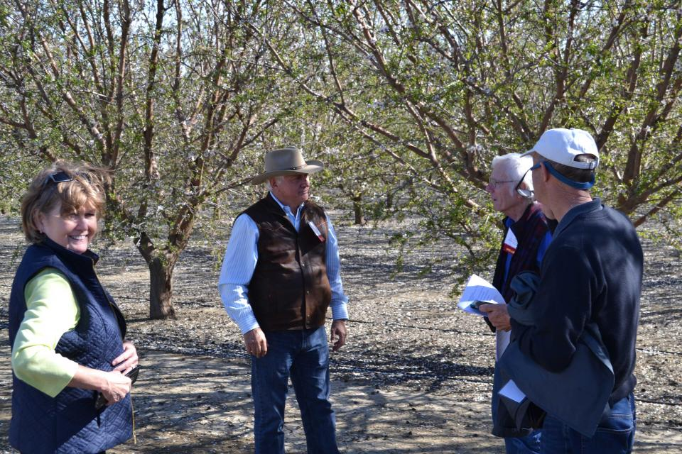 Farmer Joe Del Bosque talks with Central Valley Tour participants during a stop at his orchard.