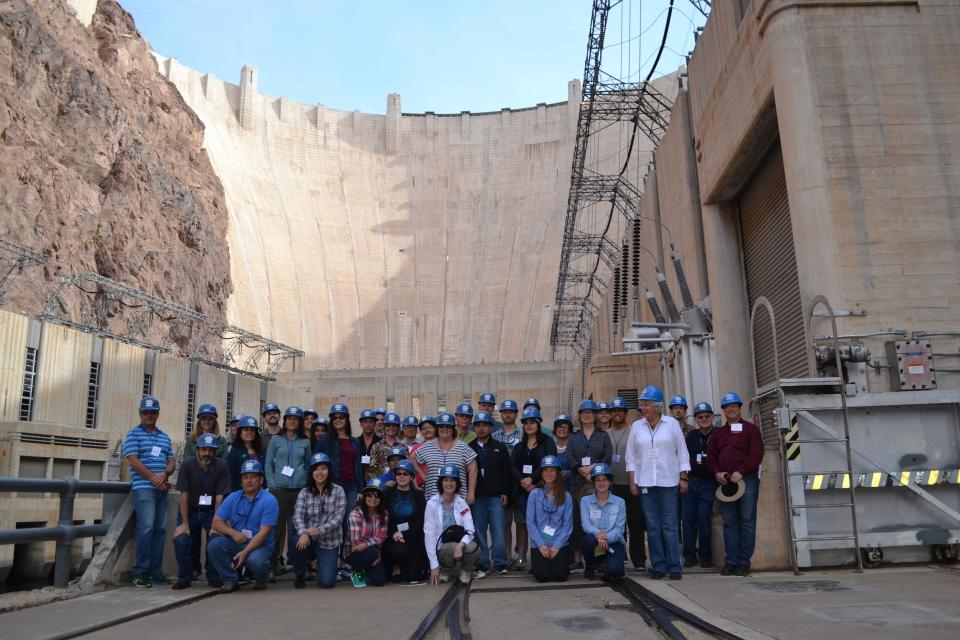 Tour group poses in front of Hoover Dam.