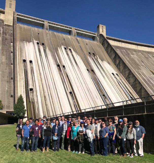 Northern California Tour participants pose in front of an imposing Shasta Dam, one of the highlights on this three-day tour.
