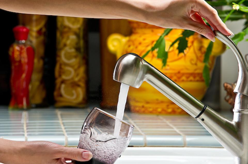 Photo of drinking water filling a glass over the kitchen sink.