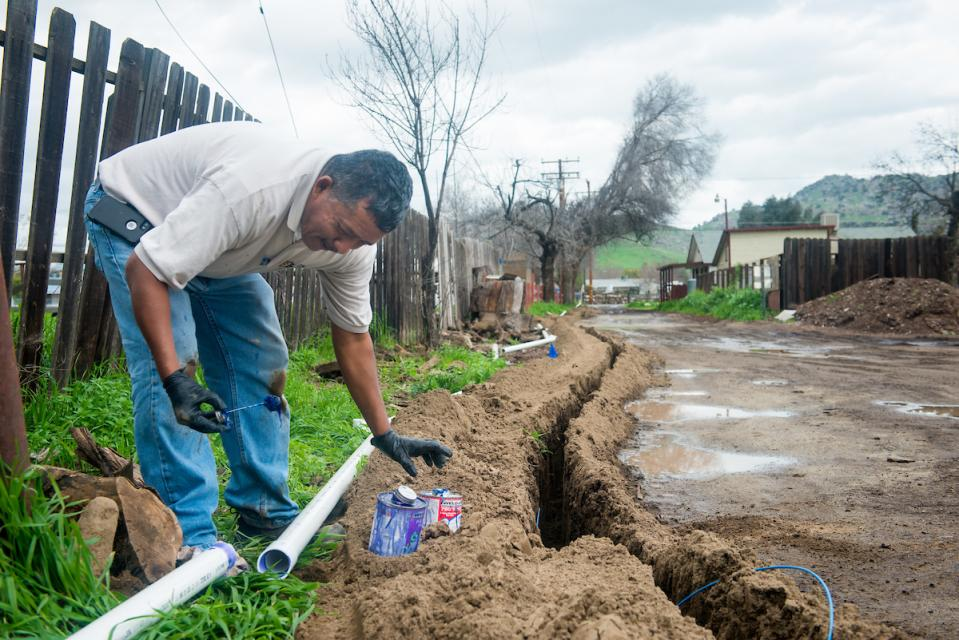 Benny Zurita installs piping from the main pipeline to residential homes in East Porterville, Calif.., in  2017.  East Porterville  residents lived with water shortage for years due to dried up wells.
