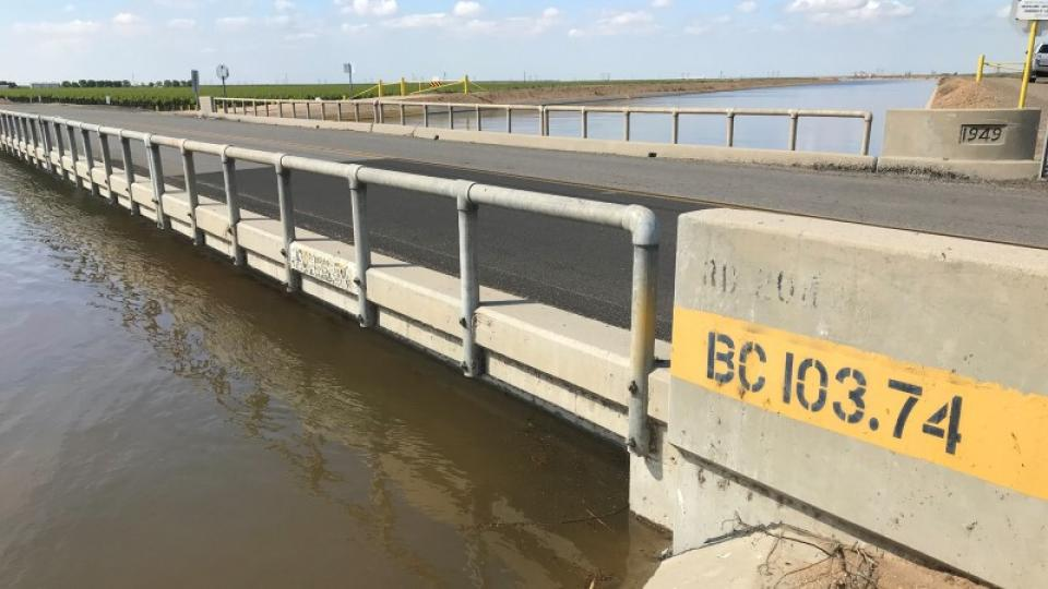 Water is up to the bottom of a bridge crossing the Friant-Kern Canal due to subsidence caused by overpumping of groundwater.